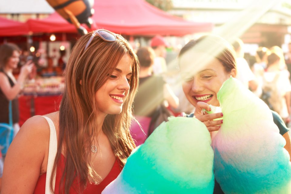 young women eating cotton candy and enjoying a street fair