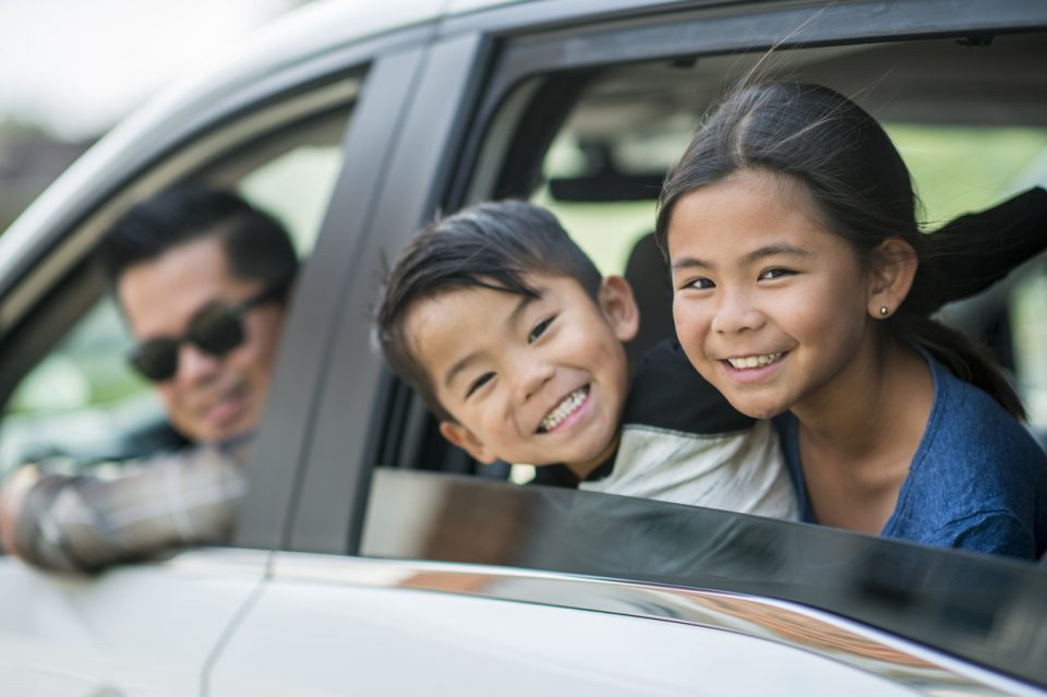 Smiling man and two kids looking out the window of their new Honda