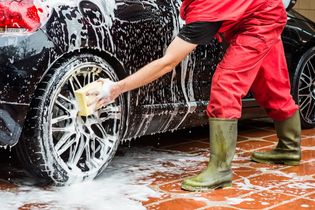 A person cleaning a black midsize sedan. with soap and water.