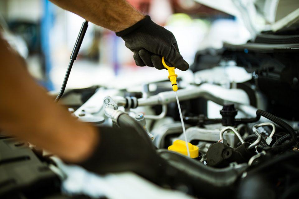 Mechanic examining car oil in a repair shop.