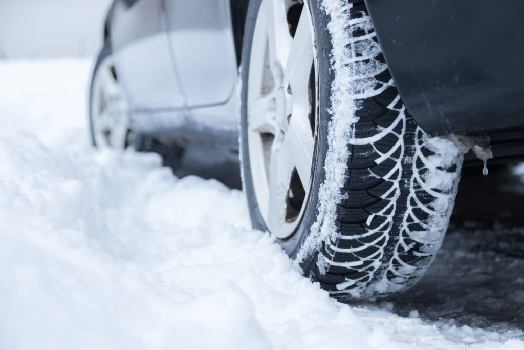 Car tire in winter on the road covered with snow, close up picture