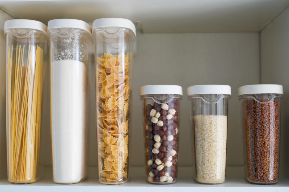 Stocked kitchen pantry with food - pasta, buckwheat, rice and sugar .