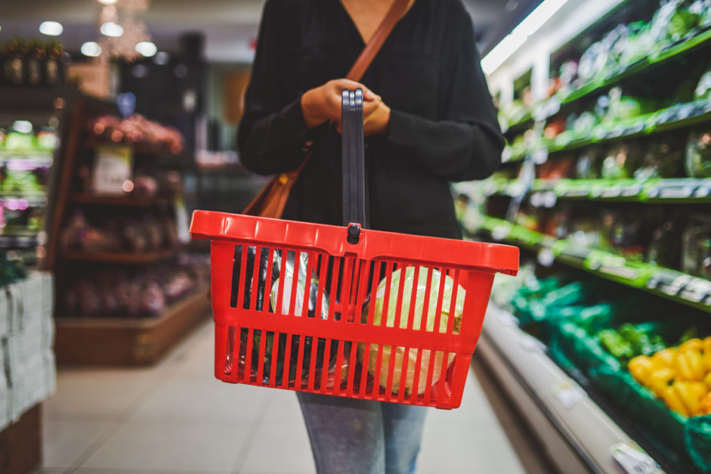 Woman shopping at a grocery store with a basket