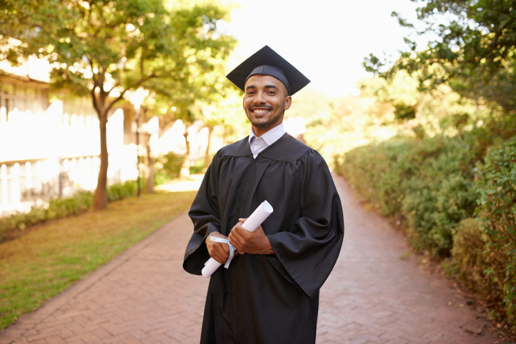 Cropped portrait of a young man posing with his degree on graduation day