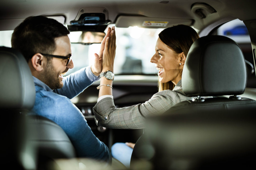 Young happy couple sitting inside of their new car and giving each other high-five