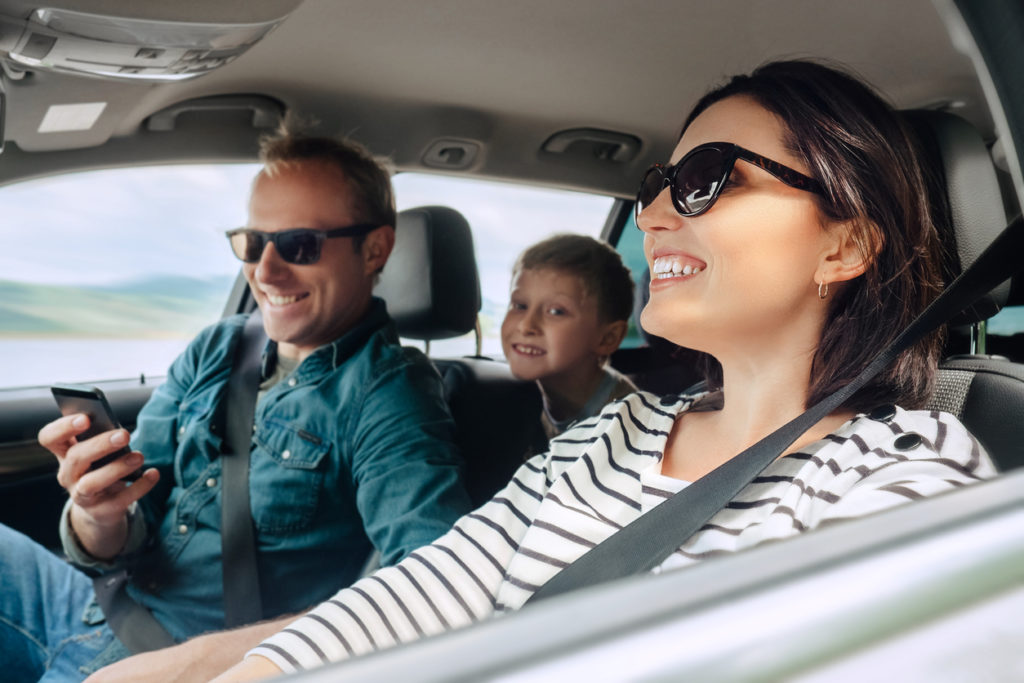 happy family happily driving on a road trip